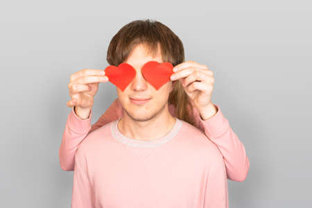 Girl stands behind young, caucasian guy and holds two red hearts in front of him, symbols of love. Couple of lovers, young, smiling, beautiful, light skinned caucasian people on light gray background.