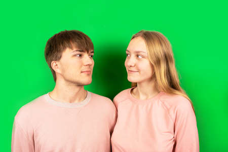 Couple of young, beautiful light skinned caucasian people are looking each other in the eyes. Blonde girl with long hair and brown-haired guy in love looking at each other on green background.