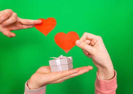 Hands of a guy and a girl hold two red hearts and a festive box with a gift on a green background close-up. Valentine's Day holiday greeting card or template for design.