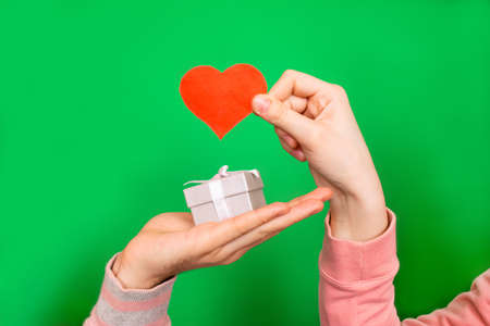 The guy's hand holds out a box with a gift, and the girl's hand holds a red heart close-up on a green background with copy space. Greeting card for Valentine's Day.