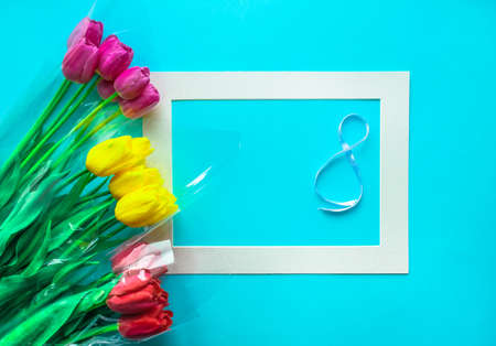 Fresh bouquets of tulips flowers on light blue background. Woman's Day 8 March greeting card. Beautiful spring concept. Flat lay, top view, copy space.