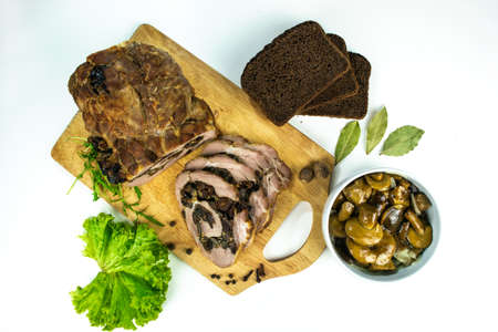 Baked meatloaf pork with prunes and mushrooms cut into pieces on a cutting board decorated with spices, bay leaves, arugula and slices of bread with marinated mushrooms in a plate on a white background. 免版税图像