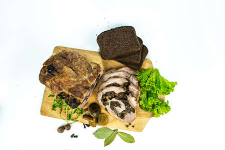 Baked meatloaf pork with prunes and mushrooms cut into pieces on a cutting board decorated with spices, bay leaves, arugula and slices of bread on a white background.
