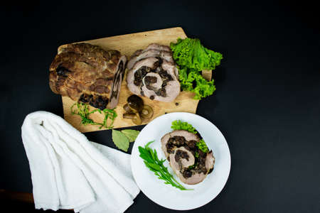 Baked meatloaf pork with prunes and mushrooms cut into pieces on cutting board decorated with bay leaves, arugula, marinated mushrooms on black background. Sandwich with meat and herbs on white plate.