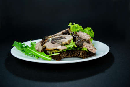 Bitten sandwich with baked meatloaf and herbs, with salad leaves and arugula for a snack on a white plate on black background. Appetizing and hearty snack.