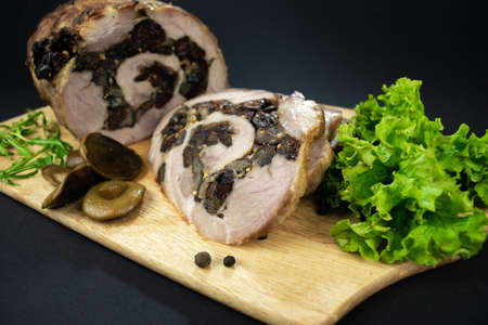 Baked meatloaf pork with prunes and mushrooms cut into pieces on a cutting board decorated with spices, bay leaves, arugula and marinated mushrooms on a black background.