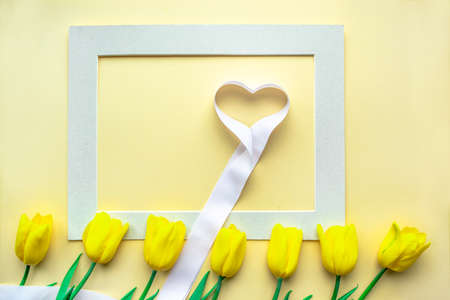 Sunny yellow flower arrangement. Yellow fresh tulips with hearts in frame on yellow paper background. Greeting card for Valentine's Day or other holiday. Selective focus. Flat lay. Copy space.