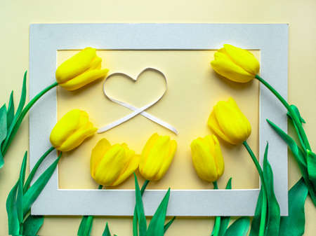 Sunny yellow spring flower arrangement. Yellow fresh tulips with heart on yellow paper background. Greeting card for Women's day, Mother's day, Valentine's Day, Family Day or other holiday. Flat lay. 免版税图像