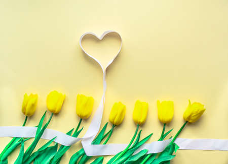 Sunny yellow flower arrangement. Yellow fresh tulips with hearts on yellow paper background. Greeting card for Valentine's Day, Mother's Day or other holiday. Selective focus. Flat lay. Copy space.