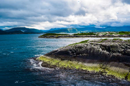 Landscape of small islands in the Norwegian Sea against the backdrop of a cloudy sky. View from the Atlantic Ocean Road, is part of the National Tourist Routes of Norway .. 免版税图像