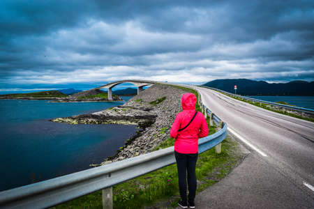 Girl tourist on the background of Storseisundet Bridge (Storseisundbrua), is most famous and longest of eight bridges that make up Atlantic Ocean Road. It is part of National Tourist Routes of Norway. 免版税图像