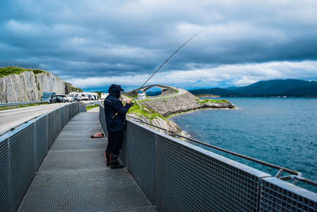 Fishermen on Hulvagen Bridge near Atlantic Ocean Road, passing through small islands in Norwegian Sea and is part of National Tourist Routes in Norway. 免版税图像
