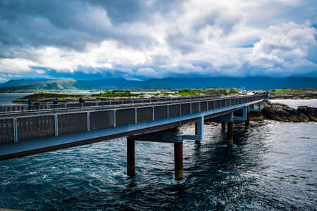 Hulvagen Bridge near Atlantic Ocean Road, passing through small islands in Norwegian Sea and is part of National Tourist Routes. One of most famous landmarks. Beautiful blue cloudy summer landscape. 免版税图像