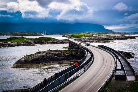Atlantic Ocean Road, passing through the several small islands in Norwegian Sea and is part of National Tourist Routes of Norway. One of most famous landmarks. Beautiful blue cloudy summer landscape. 免版税图像