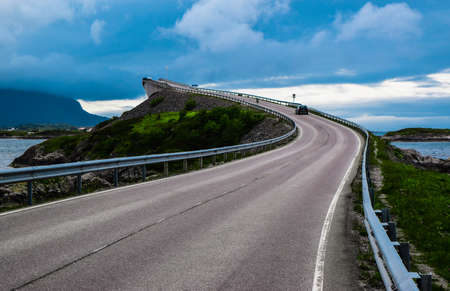 Landscape of bending Storseisundet Bridge on cloudy sky background. Storseisundbrua Bridge is the most famous and longest bridge of Atlantic Ocean Road, passing through islands in Norwegian Sea. Norway. 免版税图像
