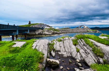 View from the small rocky island to Storseisundet Bridge in the background. Storseisundbrua is the most famous and longest bridge of Atlantic Ocean Road, passing through islands in Norwegian Sea. Norway.