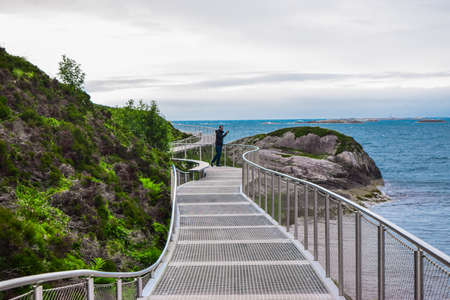 Touris man on the metal bridge of Atlantic Ocean Road islands. Atlantic Road passing through small islands in Norwegian Sea and is part of National Tourist Routes. One of most famous landmarks.