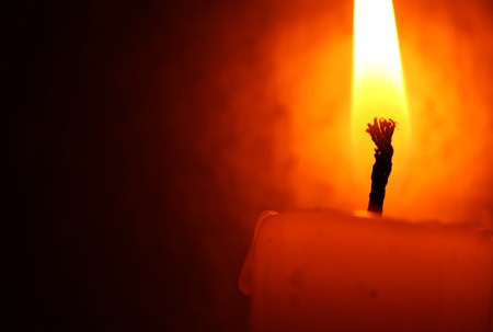 flickering: Close up of Candle with red background