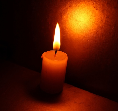 ignited: Close up of Candle with red background