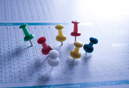 Close up of push pins stuck on some paper