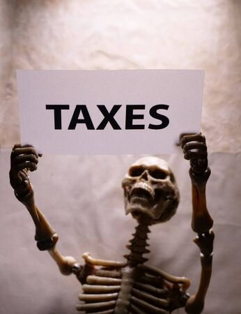 A human skeleton holding a Tax label