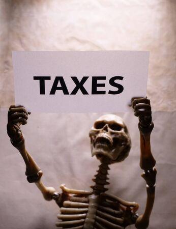 A human skeleton holding a Tax label Stockfoto - 126437276