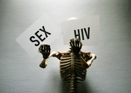 Close up of a Human skeleton holding a HIV tag Stockfoto