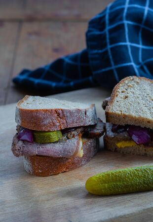 Roast beef sandwich with cucumbers rustic background