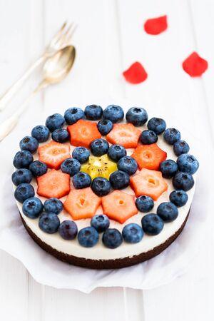 Vegan cheesecake with chocolate cake base, vegan walnut fresh cheese, vanilla pulp and fresh fruits, blueberries, strawberries and kiwi fruit