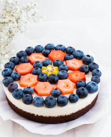 Vegan chocolate-cheese cake with vegan cream cheese, ground almonds, vanilla pulp and fresh fruits Stok Fotoğraf