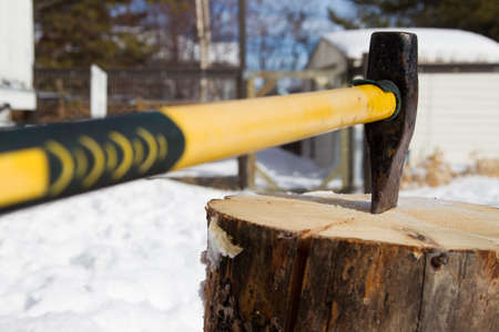 Splitting a pine log for winter firewood with an axe Stock Photo