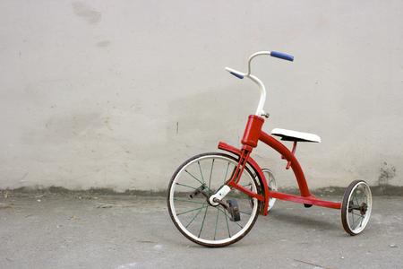 arme kinder: Red Kids Bike mit grauem Hintergrund Lizenzfreie Bilder
