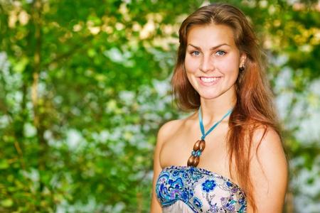 Portrait de jeune femme contre le bois vert