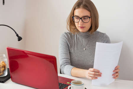 Young european woman with glasses and gray turtleneck doing paper work at home. Remote internet online classes. Isolation time. Pandemic threat. Virus outbreak.