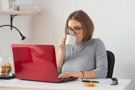Natural blonde woman wearing gray turtleneck drinking coffee while doing remote work from home. Pandemic threat. Isolation time. Virus outbreak implications.