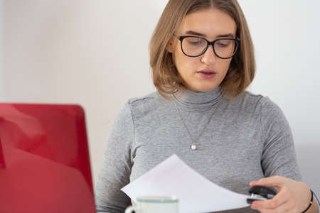 Natural blonde short hair woman doing paper work stapling documents at her desk at home. Pandemic threat. Isolation time. Virus outbreak implications