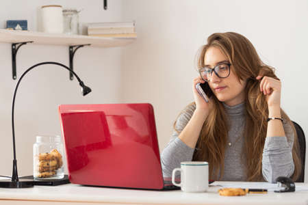 Natural blonde woman talking on the phone in front of computer and playing with her hair. Remote work from home. Isolation time. Pandemic threat. Virus outbreak implications.