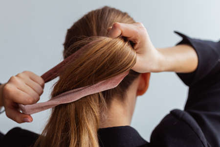 Natural blonde woman doing a ponytail, holding her hair, stop motion, back view,