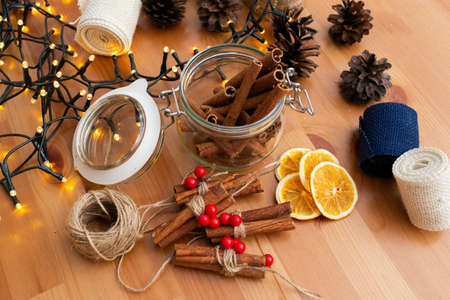 Top down view of rustic style handmade diy christmas decorations, ornaments, glass jar full of cinnamon sticks on wooden table with christmas lights, background, winter mood, theme