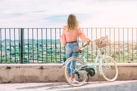 young woman with a bicycle contemplates a beautiful landscape