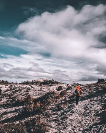 Man walking under the clouds through a place similar to the moon