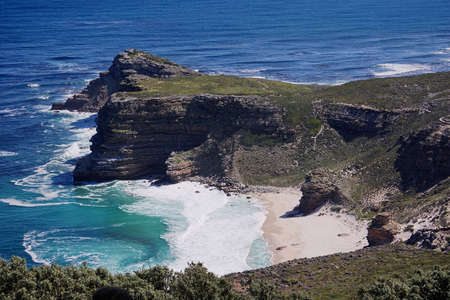 Beautiful, pristine white beach below the cliffs at Cape Point, South Africa, with blue green atlantic ocean lapping the sand
