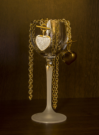 Glass of wine and gold heart necklace on a dark background