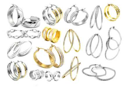 stainless background: Big set of earrings. Silver and gold stainless steel. White background. Stock Photo
