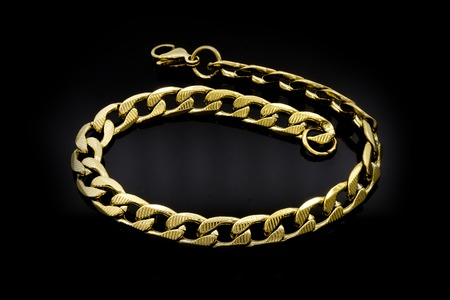 Juweel gouden armband. Roestvrij staal. Achtergrond in één kleur