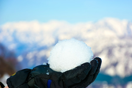 The snowball in hand with snow capped mountains.Ready to throw