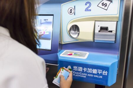 TAIPEI TAIWAN - APRIL 27, 2015: Asian woman use EasyCard value top up machine. is a contactless public transport smartcard system operated in Taipei.