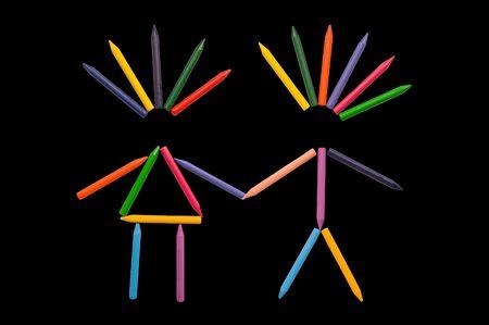 jardin de infantes: Crayones multicolores ordenados en forma de hombres y mujeres sobre fondo negro