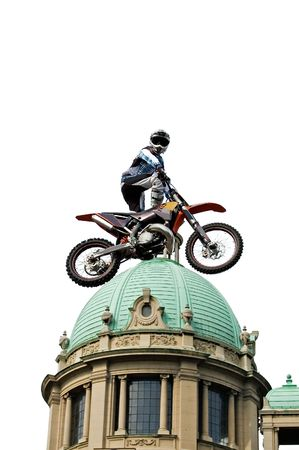 Motocross rider jumping over cupola of old building isolated on white. photo