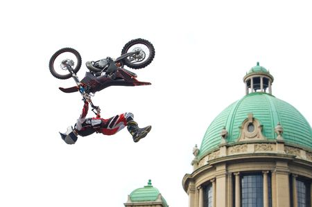 mx: Motocross rider performing back flip over cupola of old building isolated on white.